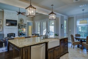 Kitchen with hanging light fixtures and granite countertops, cherry wood cabinets.