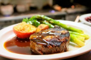 Plate of steak, asparagus, with a peach on the side.